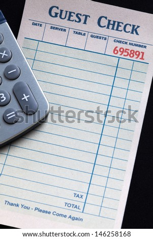 Guest Check and calculator, concept of restaurant expense.