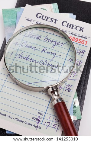 Guest Check and magnifying glass, concept of restaurant expense fraud.