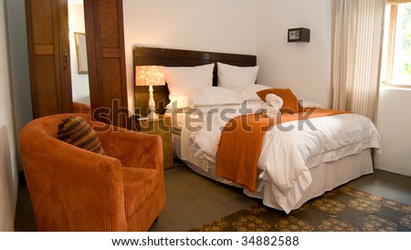 Guest house bedroom with chair, bed and cupboard - stock photo