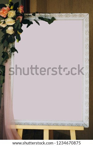 Guest list mockup. Stylish vintage board frame with space for text for guests seats and floral decorations at wedding reception in restaurant. #1234670875