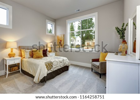 Photo of Guest modern bedroom interior with grey walls and orange pillows