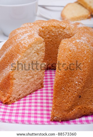 Guglhupf - Traditional Sponge Cake on Plate and Cup on Table