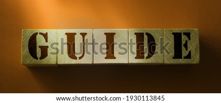 Guide Word Written on Wooden Cubes on red background. Сток-фото ©