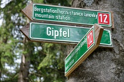 Guidepost on a tree trunk at the mountain Großer Arber pointing to the mountain station and the Gipfel ( peak ). Seen in the Bavarian Forest in Germany in August.