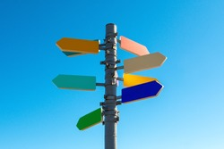 Guidepost with bright colored arrows against blue sky