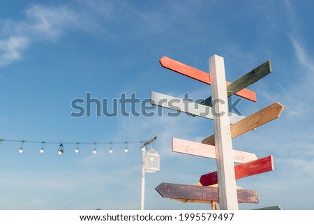Guidepost with bright colored arrows in the sunlight with blue sky background. Stock photo ©