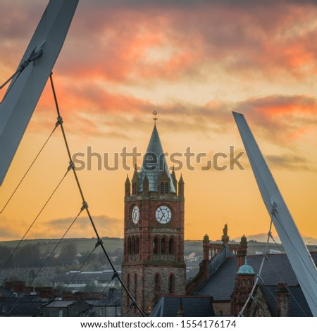 Guildhall Derry Londonderry Northern Ireland at sunset with peace bridge