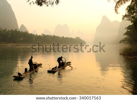 Guilin, China - October 21, 2015: Silhouette of Two Fishing Men and His Cormorants on Li River at Sunrise, Guilin, China. The Li River or Lijiang is a river in Guangxi Zhuang Autonomous Region, China.