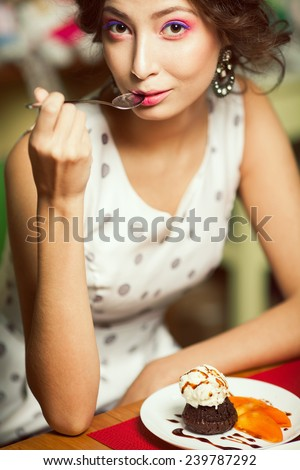 Guilty pleasure concept. Portrait of funny doll like brunette girl with retro hairdo in white trendy vintage polka-dot sleeveless dress eating cake in restaurant. Summer time. Close up. Indoor shot