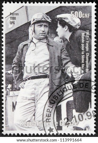 """GUINEA - CIRCA 1998. A postage stamp printed by GUINEA shows image portrait of  famous Argentinian racing car driver Juan Manuel Fangio nicknamed """"El Chueco"""", circa 1998."""