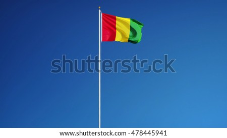 Guinea flag waving against clean blue sky, close up, isolated with clipping path mask alpha channel transparency #478445941