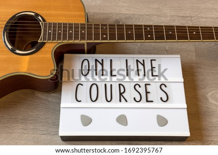 Guitar and whiteboard with text 'online courses' to exemplify online guitar lessons. ストックフォト ©