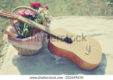 Guitar, basket with wine and bouquet of flowers. Vintage tender background. Romance, love, date, Valentine\'s day - concept