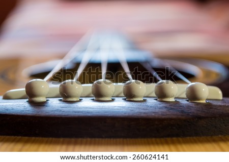 Guitar bridge and strings looking down the neck fretboard towards the tuning head