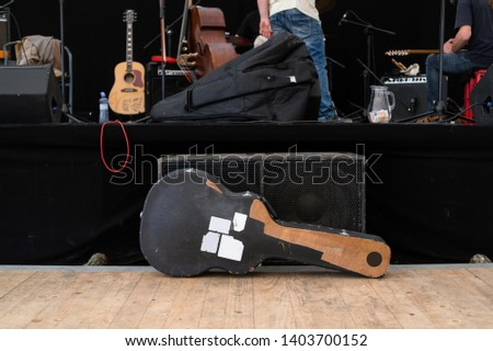 Guitar case, amplifier, muscial instruments and prepared stage before / after music concert. Authentic shot. Focus on case and low depth of field.  #1403700152