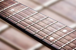 Guitar fret isolated. Music background. Wooden guitar part close up. Guitar strings background.