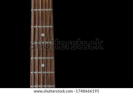 Guitar fretboard close up isolated on black stock photo