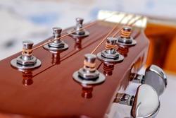 Guitar head with tuning heads. Musical instruments and music art concept. Selective focus on the pegs with the strings wind on. Close up.