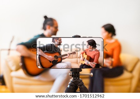 Guitar lessons tutorial with smart phone. Indoor screen shot of musical course. Technology and leisure. Professor teaching how to play an instrument. Video screen recording music online class at home. Сток-фото ©