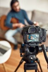 Guitar lessons. Young man sitting on sofa at home and teaching how to play guitar. Recording webinar at home. Learning music online. Focus on a camera. Stay home. E-learning. Music school online