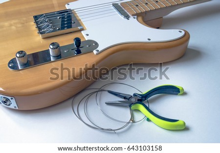 Guitar maintenance. Old guitar strings and an electric guitar. Changing guitar strings.