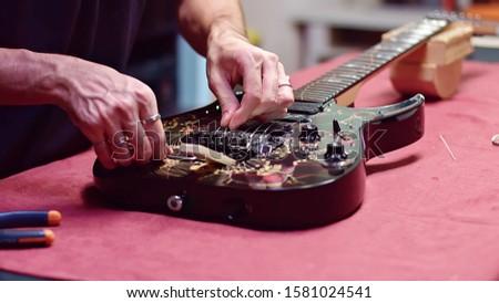 Guitar maker change strings of electric guitar