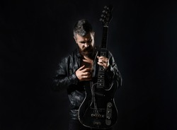 Guitar. Music instrument. Bearded man with electric guitar. Stylish man holds guitar strings. Musician, artist play, musical instrument. Guitarist in black leather jacket stands with bass guitar.Biker