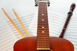 Guitar neck and fingerboard with drumsticks, recorder instrument and musical sheets on background, music scene
