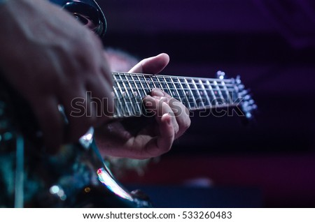Guitar neck close-up on a concert of rock music in the hands of a musician. guitarist musician