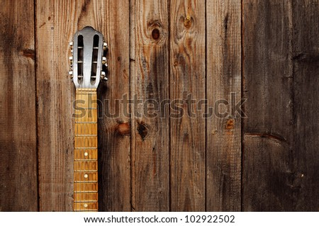 Guitar Neck on the old wooden wall