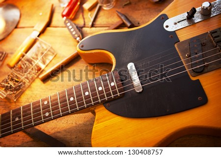 Guitar on guitar repair desk. Vintage electric guitar on a guitar repair work shop. Single cutaway electric guitar, amber color.