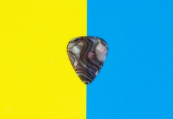 Guitar pick on colored blue yellow paper background.
