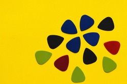 Guitar picks are placed on a yellow background
