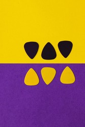 Guitar picks, placed on a half yellow half purple background