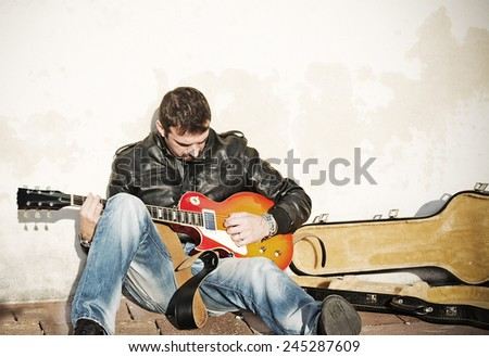 guitar player against the wall with an open guitar case
