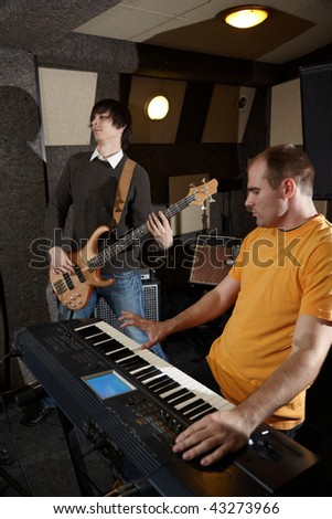 guitar player and keyboard player is working in studio. focus on distant part of synthesizer