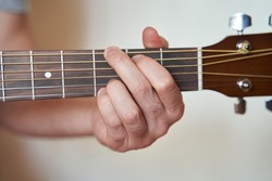 Guitar Player Hand or Musician Hand in G Major Chord on Acoustic Guitar String with soft natural light in close up view