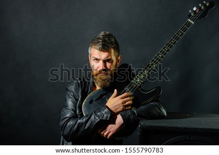 Guitar player in jacket with electric guitar. Music hobby. Fashionable guitarist with classic instrument. Bearded man with guitar. Concert tour. Rock or punk music concert. Attractive man with guitar
