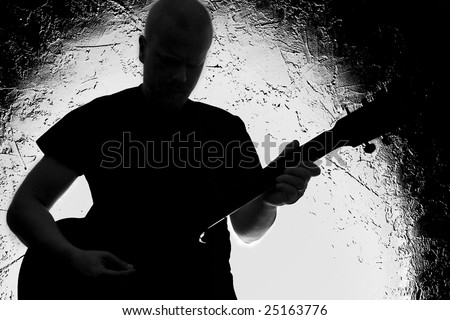 Guitar player on stage. Silhouette. Lighted background.Strong contrast. Black&white.