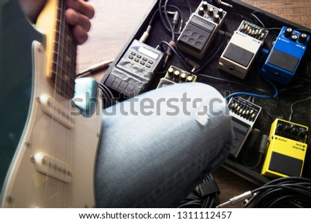 Guitar player or guitarist with audio processing effects on a studio floor. Electric guitar and stomp box type effectors and cables on studio floor.