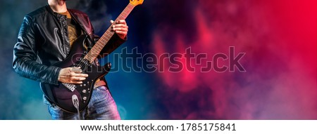 Guitar player performs on stage. Rock guitarist plays solo on an electric guitar. Artist and musician performs like rockstar.  Foto stock ©