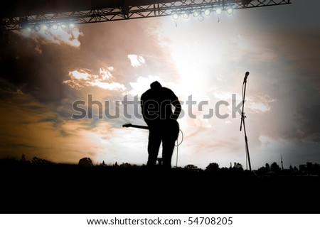 Guitar player playing a outdoor concert at sunset