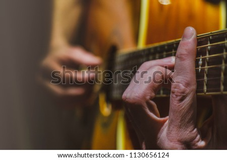 guitar player playing guitar picking chords