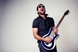 Guitar player. Rockstar playing on guitar. Wearing sunglasses
