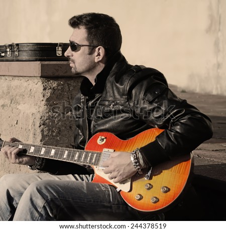 guitar player with electric guitar at sunset in vintage tone