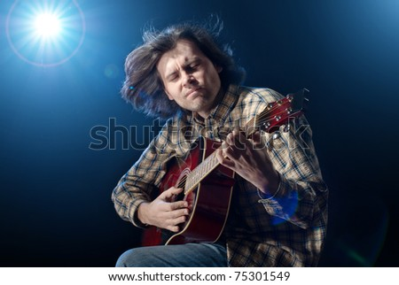Guitar playing. Man with long hair playing acoustic six-string guitar. Isolated on black background.