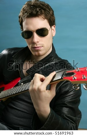guitar rock star man sunglasses and leather perfect jacket over blue