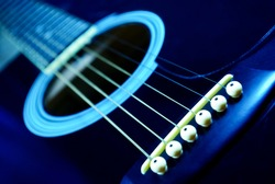 Guitar side view, strings and fingerboard with a shallow depth of field