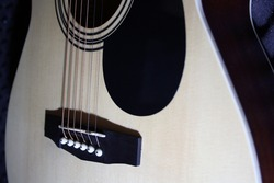 Guitar strings, light wood guitar body. Space for text.