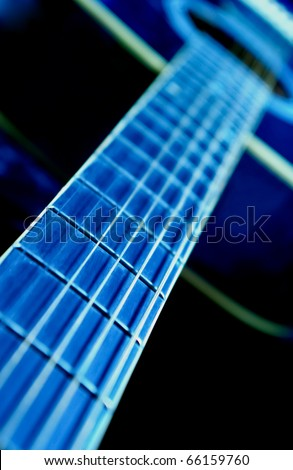 Guitar strings side view and fingerboard with a shallow depth of field